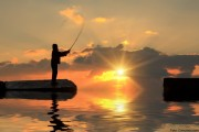 Fisherman on pier at sunset