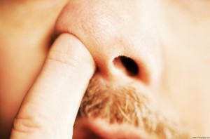 Man's finger in nose