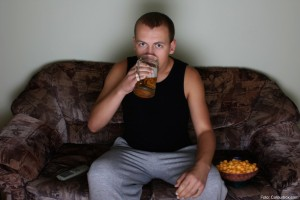 young man watching tv and drinking beer