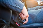 Driver in business suit fastens his seat himself automobile seat belt