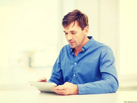 technology and lifestyle, distance learning concept - handsome man working with tablet pc at home
