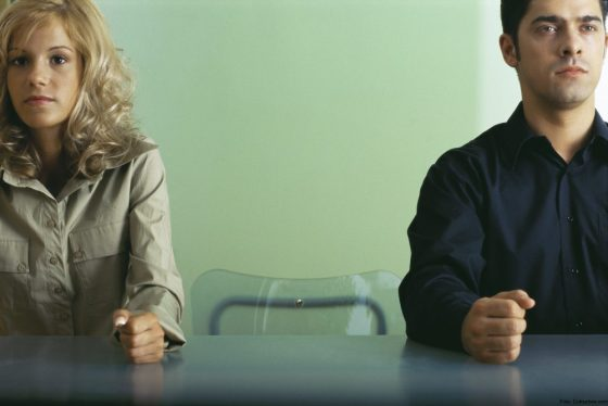 ©Frédéric Cirou/AltoPress/Maxppp ; Man and woman sitting at table with empty chair between them, both clenching fists