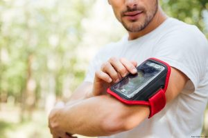 Closeup of young man athlete using mobile phone in handband outdoors in the morning